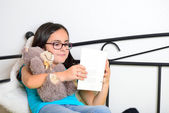 Girl with teddy bear reading a book — Stock Photo