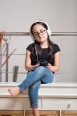 Jolie fille avec des lunettes, écouter de la musique — Photo