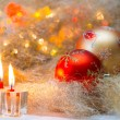Christmas balls with candles on the background lights — Stock Photo #57452607