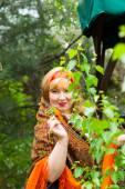 Cheeked Russian cheerful young woman in the green of spring foli — Stock Photo