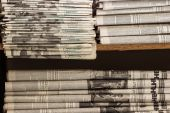 A stack of old newspapers lie on the shelf — Stock Photo