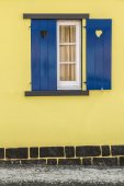 Blue window with hearts and yellow wall — Stock Photo