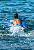 Young Boy on Airbed Splashing in the Sea — Stock Photo