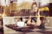 Brunette woman sitting at the cafe reading book, studing and drinking coffee and talking on the phone. Copy Space — Stock Photo