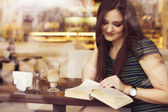 Brunette woman sitting at the cafe reading book, studing and drinking coffee. Copy Space — Stock Photo