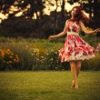Beautiful brunette caucasian woman in white and red dress at the park in red and yellow flowers on a summer sunset dancing in the meadow. Copy Space — Stock Photo #54763841