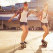 Two Brunette teenage girls friends in hipster outfit (jeans shorts, keds, plaid shirt, hat) with a skateboard at the park outdoors. Copy space — Stock Photo #54828541