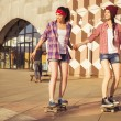 Two Brunette teenage girls friends in hipster outfit (jeans shorts, keds, plaid shirt, hat) with a skateboard at the park outdoors. Copy space — Stock Photo #54829373