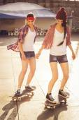 Two Brunette teenage girls friends in hipster outfit (jeans shorts, keds, plaid shirt, hat) with a skateboard at the park outdoors. — Stock Photo