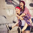 Two Brunette teenage girls friends in hipster outfit (jeans shorts, keds, plaid shirt, hat) with a skateboard at the park outdoors. Copy space — Stock Photo #54836089