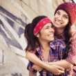 Two Brunette teenage girls friends in hipster outfit (jeans shorts, keds, plaid shirt, hat) with a skateboard at the park outdoors. Copy space — Stock Photo #54836657