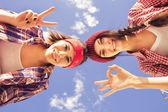 两个黑发少女朋友在行家装备 (牛仔短裤,keds,格子衬衫,帽子) 与滑板公园户外. — 图库照片