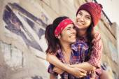 Two Brunette teenage girls friends in hipster outfit (jeans shorts, keds, plaid shirt, hat) with a skateboard at the park outdoors. Copy space — Stock Photo