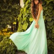 Beautiful blonde with a long curly hair in a long evening dress in motion outdoors near retro vintage building all in leaves in summer sunset — Stock Photo #54887639
