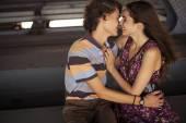 Joven pareja besándose en la luz del sol de verano en un puente construc — Foto de Stock