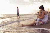 Kum sahil su üzerinde seyir deniz kenarında oturan kadın — Stok fotoğraf