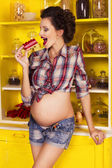 Beautiful brunette woman on a 7th month pregnancy in plaid shirt — Stock Photo