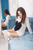 Beautiful brunette woman on a 7th month pregnancy in white sweat — Stock Photo