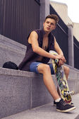 Young blonde guy on skateboard in casual outfit in the urban cit — Stock Photo