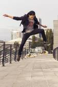 Young blonde guy jumping on skateboard in casual outfit in the u — ストック写真