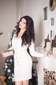 Beautiful brunette woman in white dress in new year decorated in — Stockfoto