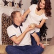 Loving couple celebrating christmas and new year at home sitting — Stock fotografie #57479435