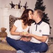 Loving couple celebrating christmas and new year at home sitting — Stock Photo #57479757