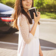 Beautiful brunette caucasian young woman standing near black car — Stock Photo #77814268