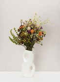 Dried flowers in porcelain vase — Stock Photo