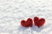 Two red hearts with face in snow - happy — Stock Photo