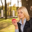 Beautiful girl stands near a tree and looking at an apple in her — Stock Photo #59095649