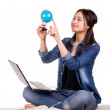 Girl sitting on the carpet with a globe, a laptop and books — Stock Photo #76882455