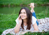 Girl with a phone resting on the lawn — Stock Photo