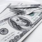 One hundred dollar bills lie on plate — Stock Photo #61497147