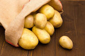 Sack of potatoes on wood — Stock Photo