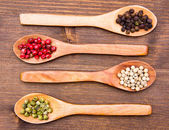 Wooden spoons with mixed peppers on wood from above — Stock Photo