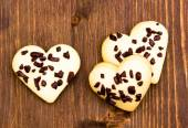 Cookies in the shape of heart with chocolate on wood from above — Stock Photo