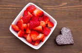 Sweet heart-shaped and strawberries on wood from above — Stock Photo