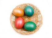 Basket with colored eggs from above — Stock Photo