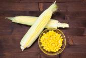Bowl of corn cobs and wood on top — Stock Photo