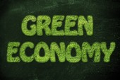 Green economy writing made of grass texture — Stock Photo