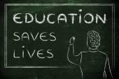 Teacher writing on blakboard: education saves lives — Stockfoto