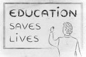 Teacher writing on blakboard: education saves lives — Zdjęcie stockowe