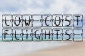 Slova nízkonákladové lety na pláži pozadí — Stock fotografie