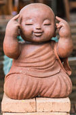 Smiling buddhist novice made of clay, Thai style — Stock Photo