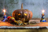 Halloween still life with pumpkins, apple, candles and rosary — Stock Photo