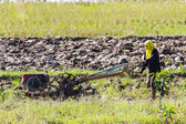 Asia Farmer using tiller tractor in rice field — Stock Photo
