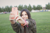 Beautiful young woman taking a selfie with phone — Stock Photo