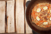 Traditional central asia pilaf in kazan on logs — Stock Photo