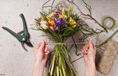 Hands of florist making bouquet spring flowers — Stock Photo